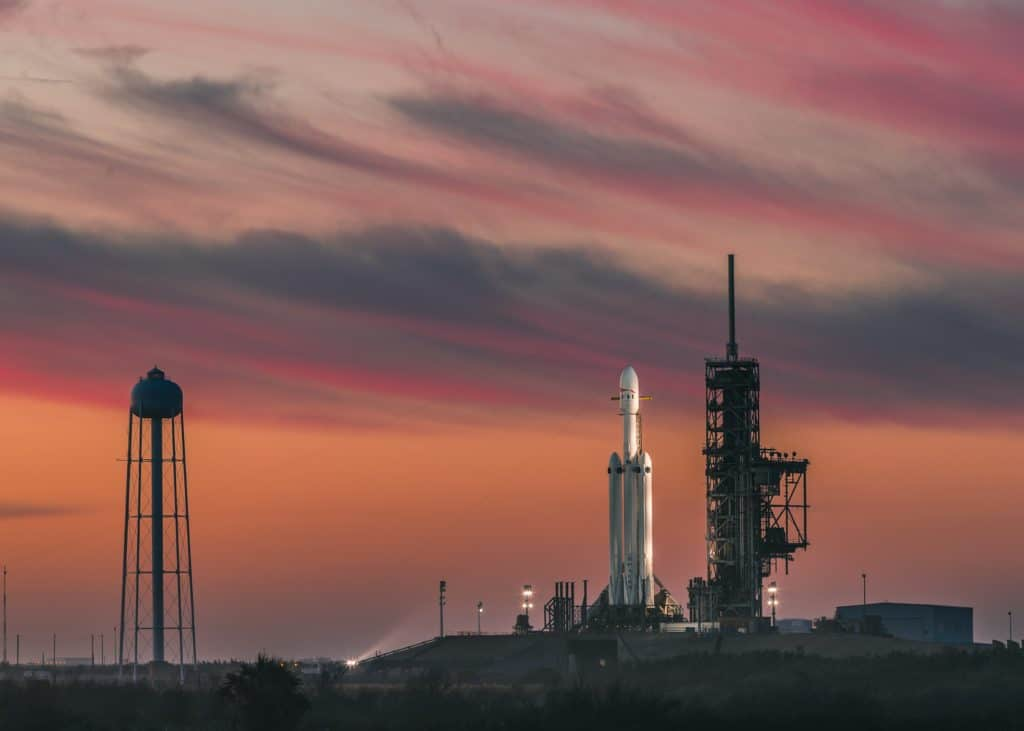 white rocket under cloudy red skies