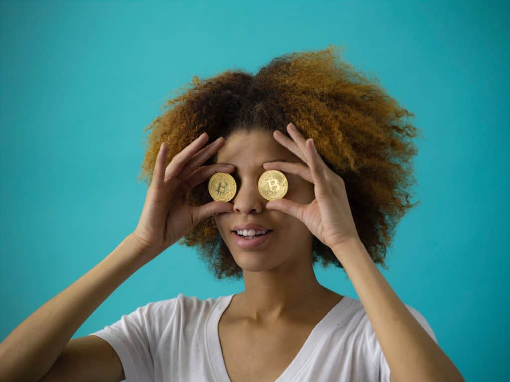 woman holding bitcoins in front of her eyes