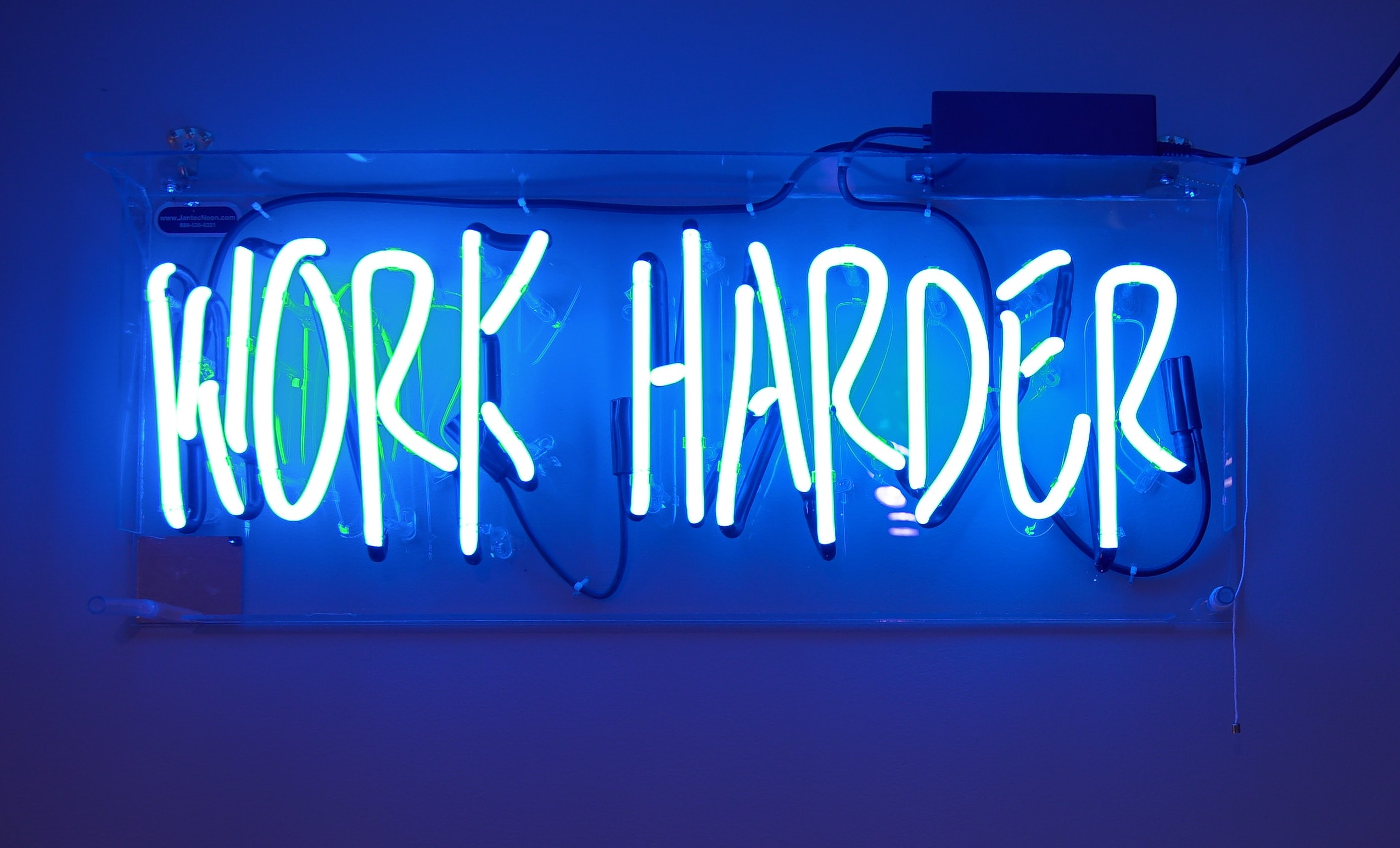 Body copy image of a neon sign saying 'Work harder'