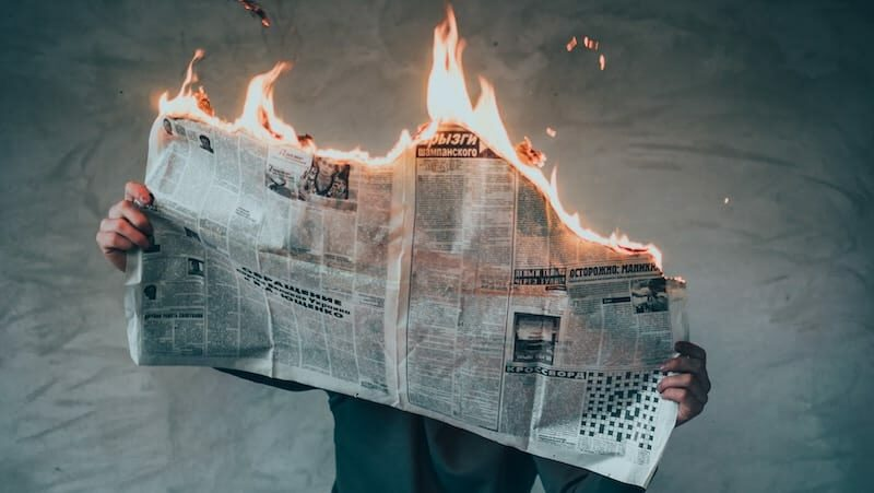 Hero image of a newspaper on fire
